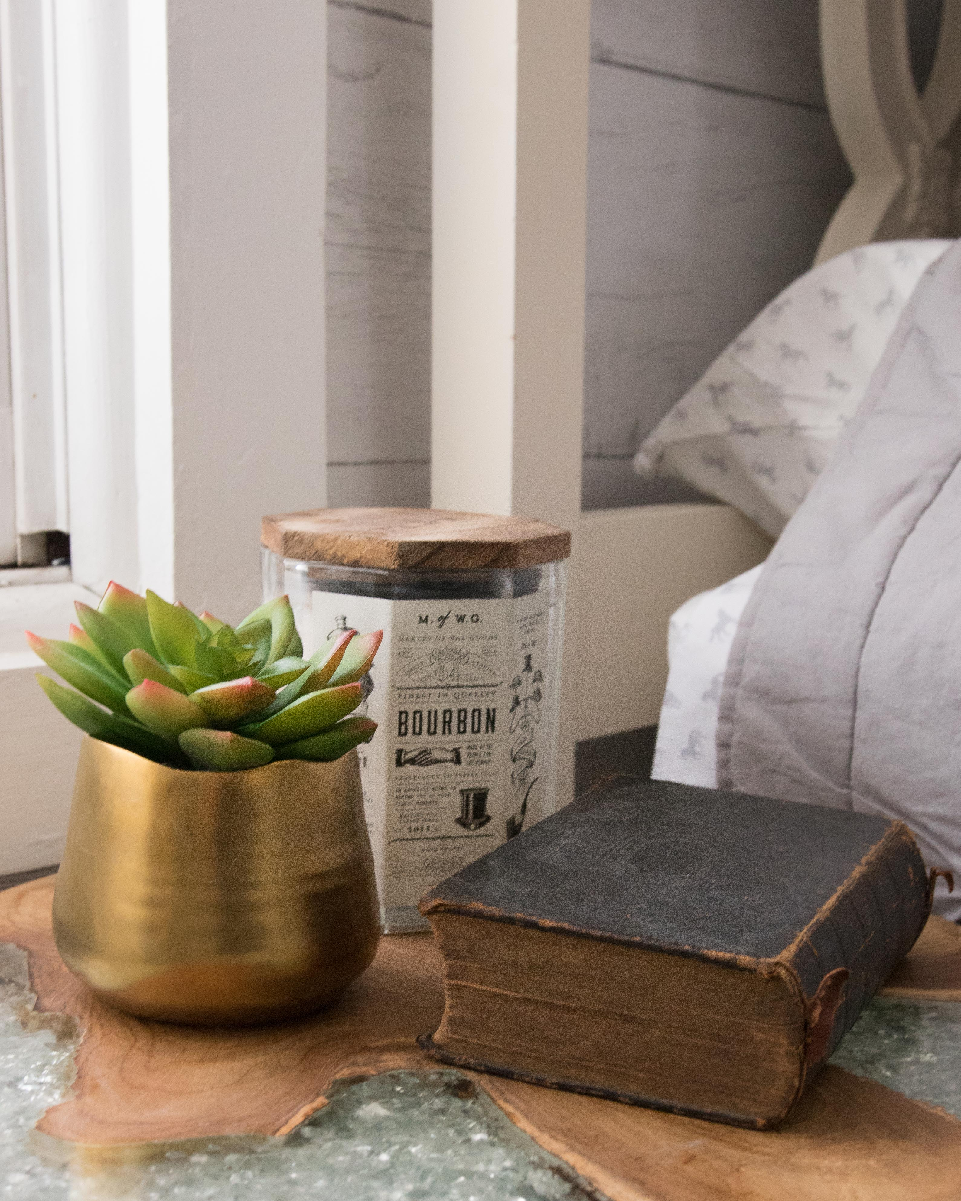 vintage book, bourbon candle, and succulent on a crystal side table