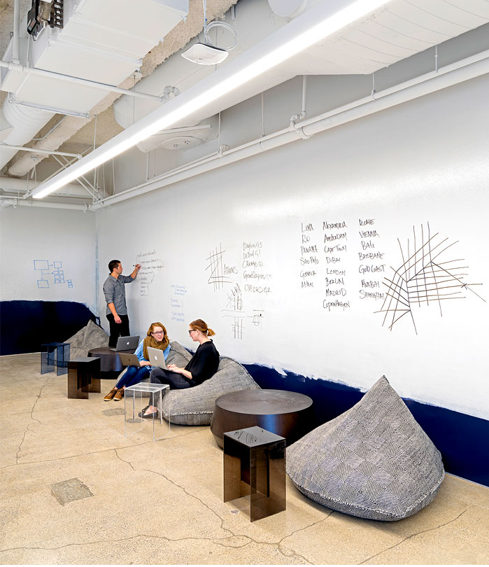 Minimalist modern office design with bean bags in meeting room and dry erase walls