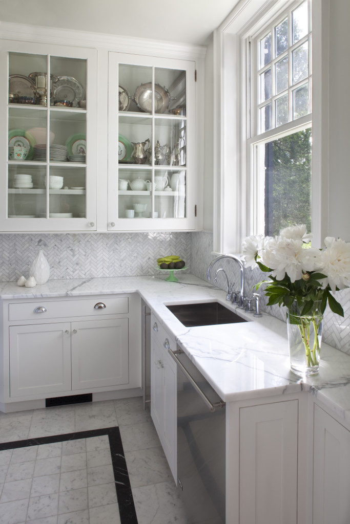 Herringbone marble backsplash in a traditional kitchen with white cabinetry